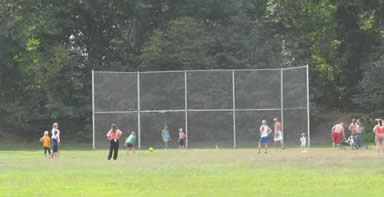 people of all ages playing kickball on the sports field