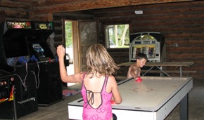2 kids playing air hockey in the lodge