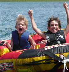 Two boys tubing -- one is excited, the other is afraid.